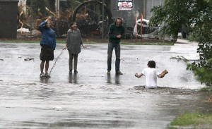A group of people watches a man wade chest-deep through the Rio de Flag as a flash flood fills the drainage at the intersection of South Leroux Street and Phoenix Avenue. (Jake Bacon/Arizona Daily Sun/file photo)